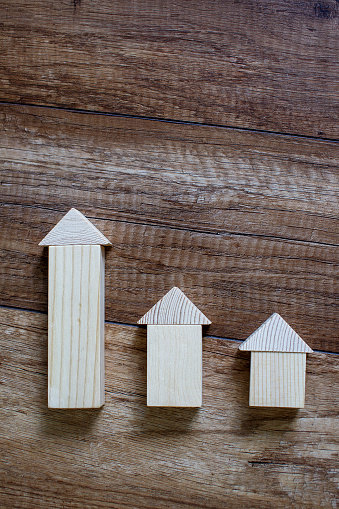 wooden toy houses in a row according to size