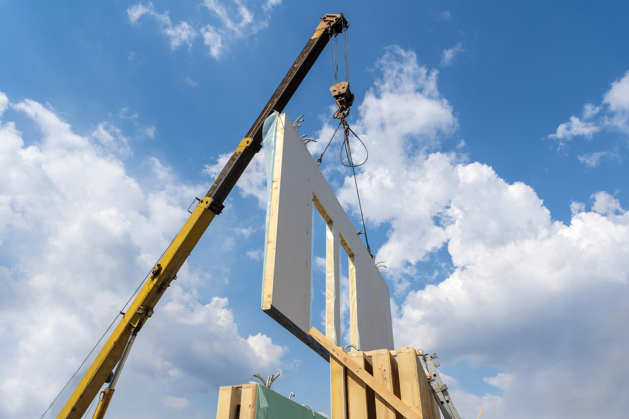 Process Of Crane Construction Of New And Modern Modular House From Composite Sip Panels Against Background With Beautiful Blue Sky