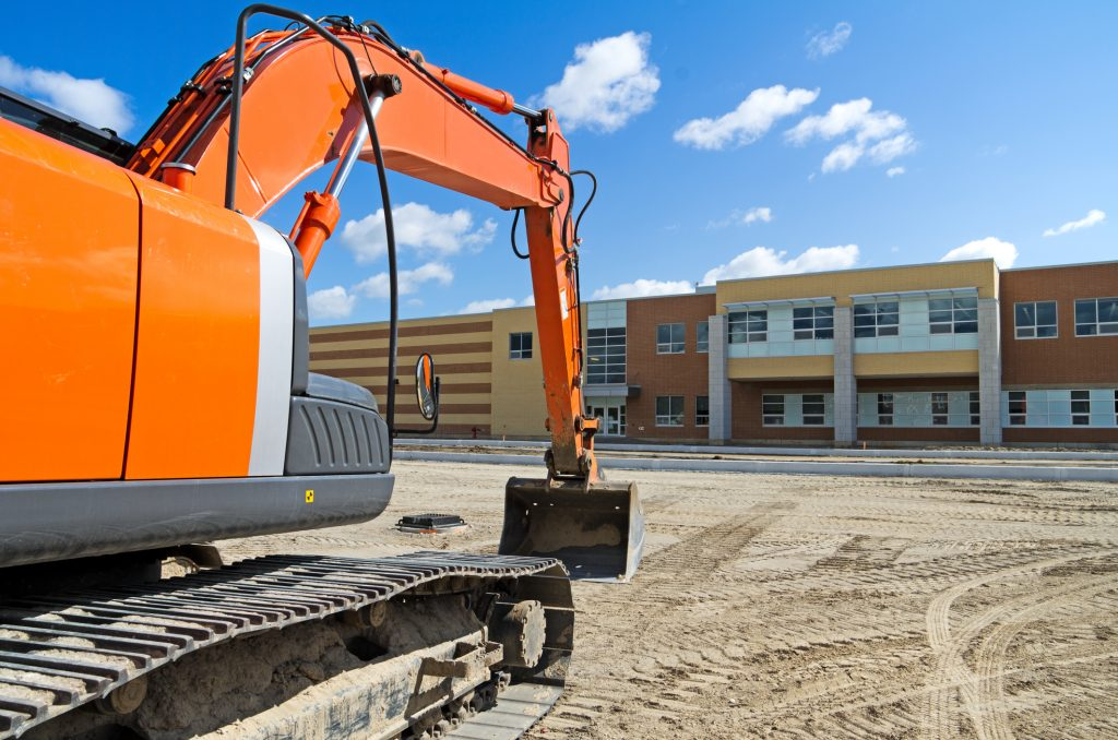 A bright orange construction excavator in the recently graded parking lot of a new high school representing modular buildings