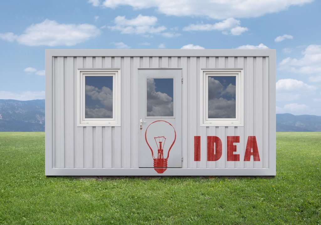 """Stencil graffiti on a shipping container structure on field with a cloudy sky background view: Red colored light bulb and """"IDEA"""" text."""