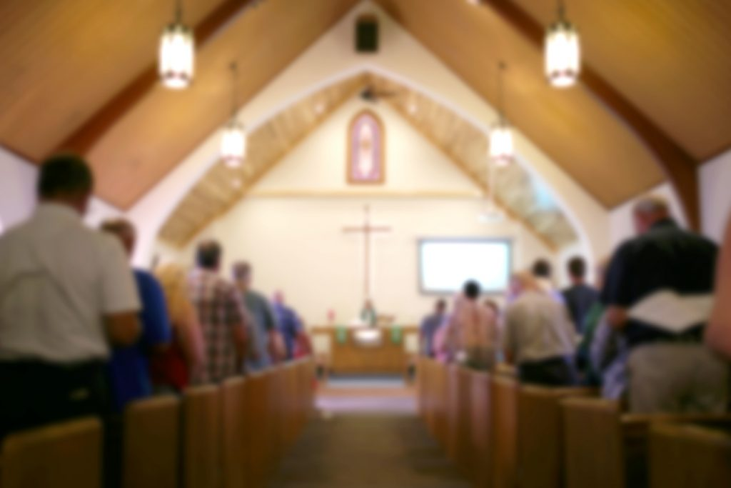 modular church buildings - A blurred photo of the inside of a church sanctuary that is filled with people in the pews, and the pastor stands under a large cross at the altar.